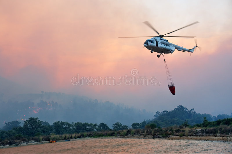 Il grande elicottero di salvataggio del fuoco ottiene l'acqua fotografia stock