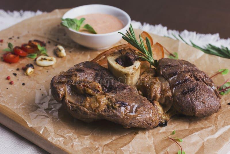 Il grande pezzo di carne arrostito sull'osso con salsa e le spezie immagini stock libere da diritti