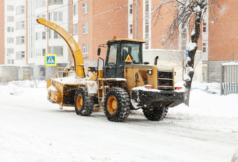 Il grande sgombraneve a turbina giallo pulisce la neve sulle vie di una città fotografia stock