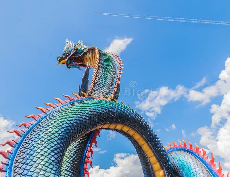 Il grande simbolo del Naga di Phaya, con il fondo della nuvola del cielo blu, il pubblico dominio nel villaggio ed il tempio in T fotografia stock libera da diritti