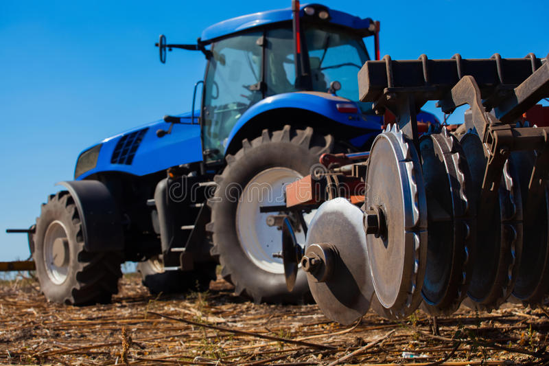 Il grande trattore blu ara il campo e rimuove il resti del girasole precedentemente falciato immagine stock
