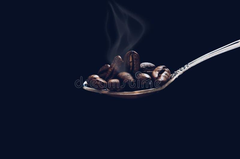 Il grano ha arrostito il cucchiaio di caffè con fumo su fondo scuro con ombreggiatura fotografia stock