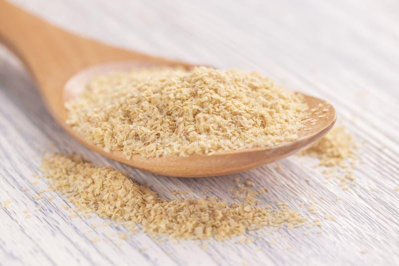 Il grano ha germinato i semi in cucchiaio di legno su una tavola di legno bianca Le briciole hanno sparso intorno immagini stock libere da diritti