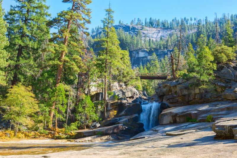 Il grembiule d'argento è una cascata liscia sopra granito lucidato, fra il Nevada e le cadute primaverili alla mattina soleggiata immagine stock