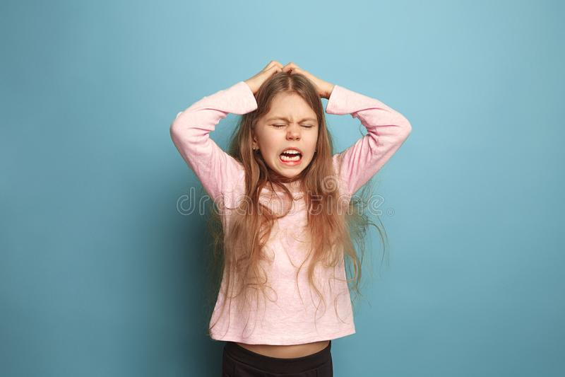 Il grido Ragazza teenager su un fondo blu Concetto di emozioni della gente e di espressioni facciali fotografia stock libera da diritti