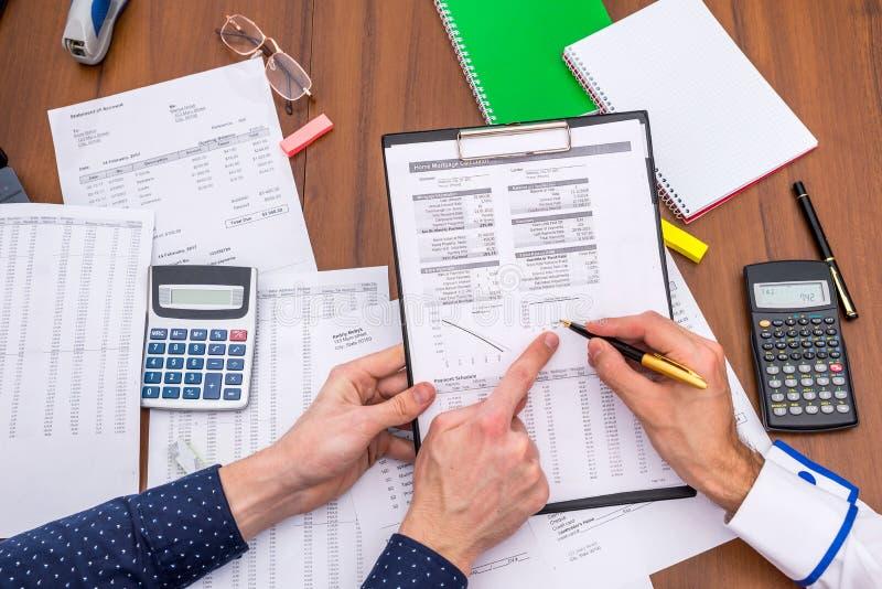 Il gruppo analizza le spese di esercizio del bilancio annuale immagine stock libera da diritti