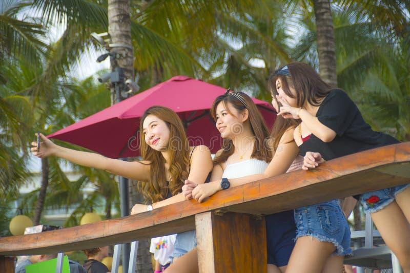 Il gruppo con le giovani donne cinesi e coreane asiatiche felici ed attraenti che vanno in giro, amiche che godono delle feste sc immagine stock
