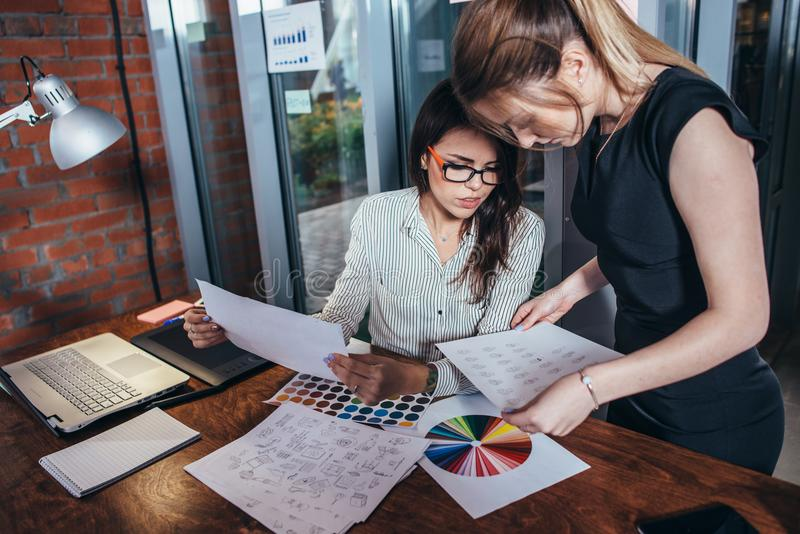 Il gruppo creativo dei grafici che lavorano al nuovo progetto facendo uso dei campioni di colore e gli schizzi degli elementi del immagine stock