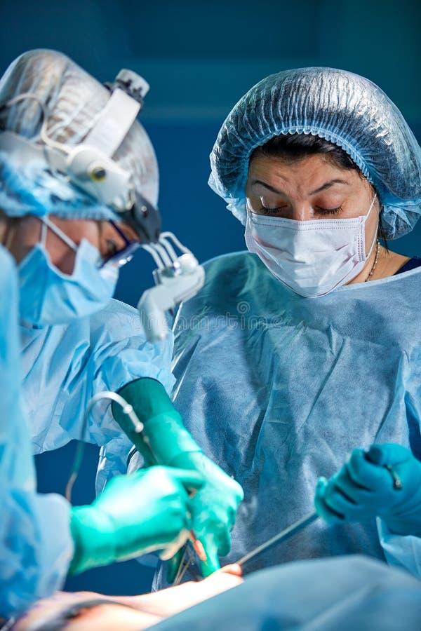 Il gruppo dei chirurghi fa un'operazione dilagante Ritratto del primo piano dei chirurghi Lavoro con uno strumento di coagulazion fotografia stock libera da diritti