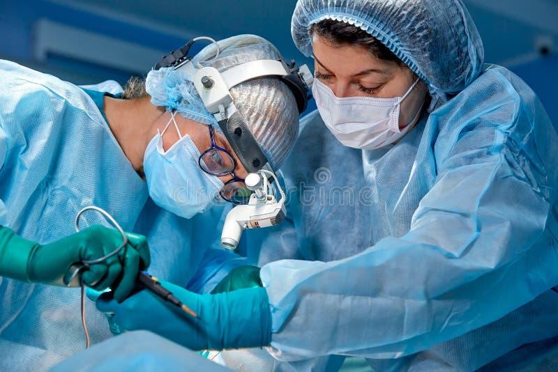 Il gruppo dei chirurghi fa un'operazione dilagante Ritratto del primo piano dei chirurghi Lavoro con uno strumento di coagulazion fotografie stock