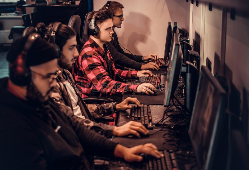 Il gruppo dei gamers adolescenti gioca in un video gioco con diversi giocatori sul pc in un club di gioco immagini stock libere da diritti