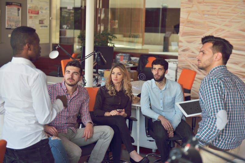 Il gruppo dei giovani in ufficio moderno ha la riunione e 'brainstorming' del gruppo mentre lavora al computer portatile ed al ca immagini stock