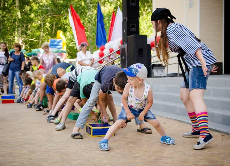 Il gruppo dei ragazzi che gioca il gioco di divertimento si passa la scatola fra le loro gambe al partito del pirata immagine stock