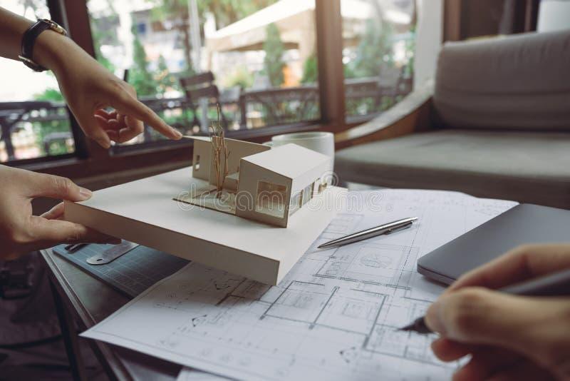 Il gruppo del collega degli architetti che discutono e che indicano al modello di architettura con la carta da disegno ed il comp fotografia stock