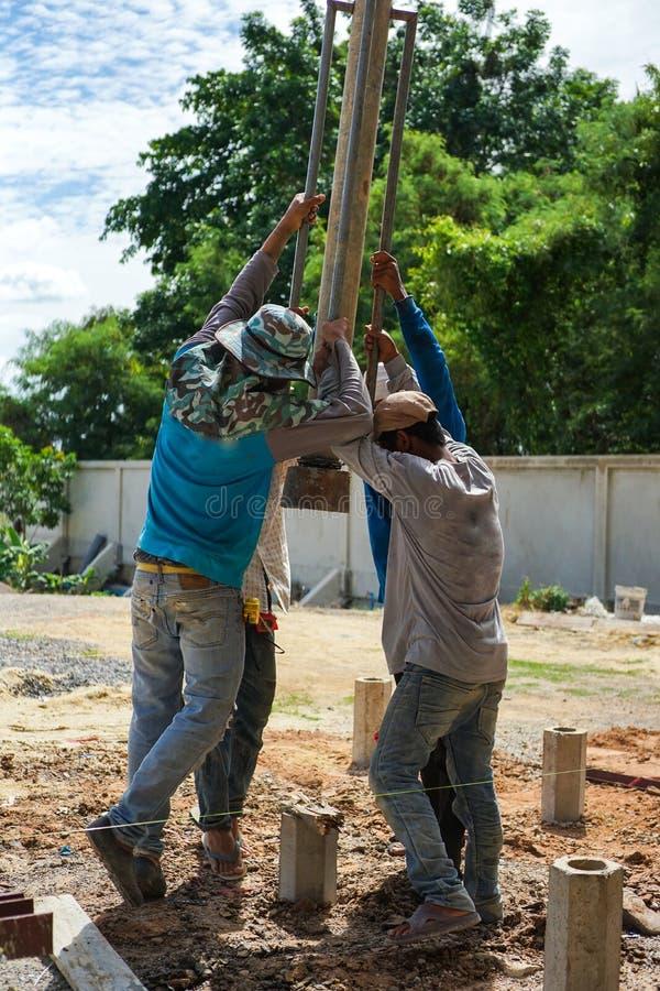 Il gruppo del ritratto di lavoratori ha colpito i mucchi concreti in terra dagli strumenti d'acciaio manuali al cantiere immagini stock libere da diritti