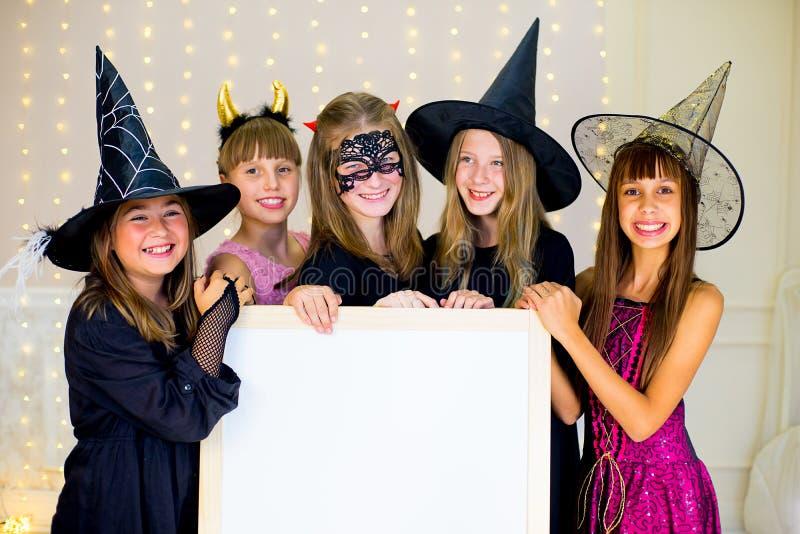 Il gruppo di adolescenti che indossano Halloween costumes la posa con il bianco immagine stock libera da diritti