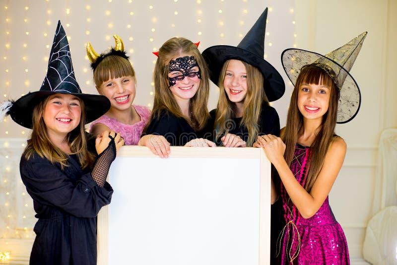 Il gruppo di adolescenti che indossano Halloween costumes la posa con il bianco immagini stock libere da diritti