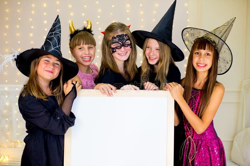 Il gruppo di adolescenti che indossano Halloween costumes la posa con il bianco fotografia stock
