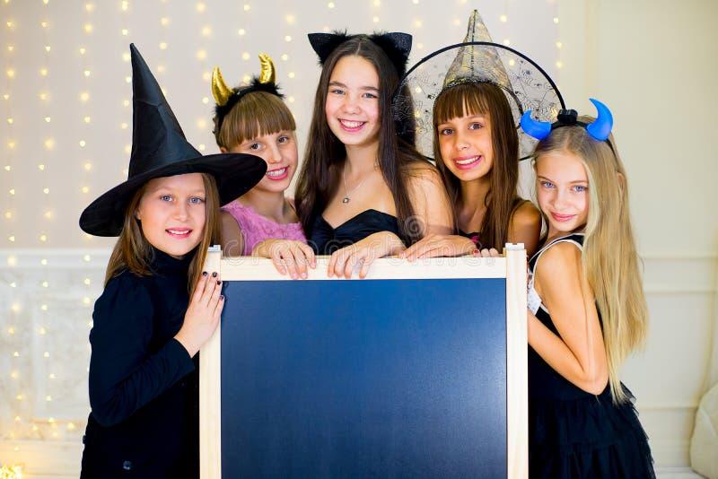 Il gruppo di adolescenti che indossano Halloween costumes la posa con il nero fotografia stock libera da diritti