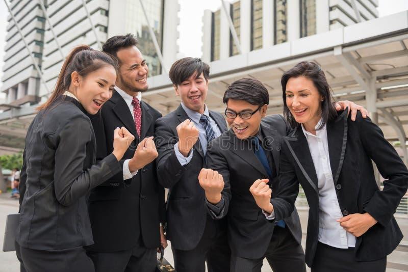 Il gruppo di affari celebra il successo con le armi alzate fotografia stock