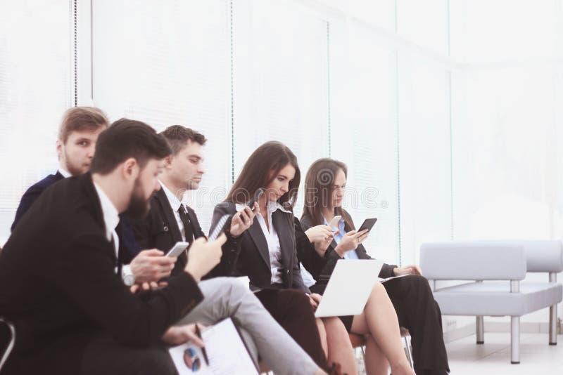 Il gruppo di affari utilizza i computer portatili e gli smartphones mentre si siede nell'ingresso dell'ufficio Generazione di sti immagine stock libera da diritti