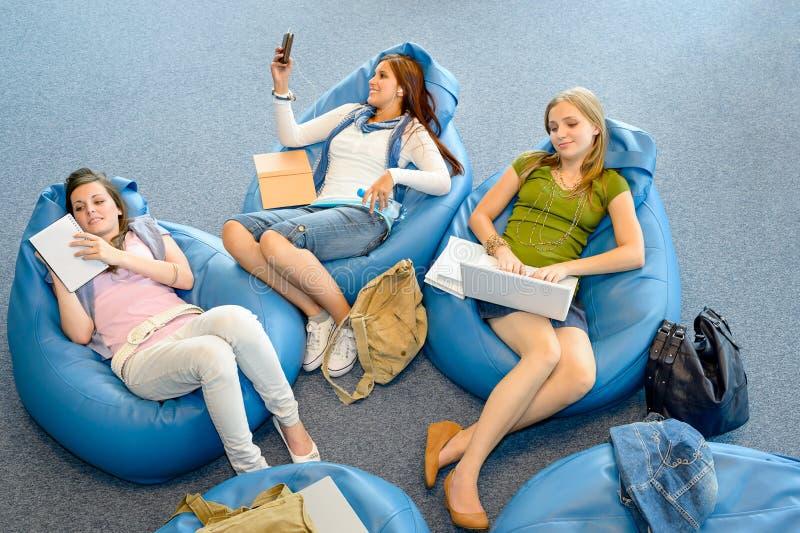 Il gruppo di allievi che si trovano sul beanbag si distende immagini stock libere da diritti