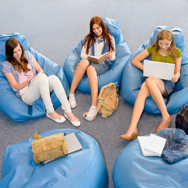 Il gruppo di allievi si distende sul beanbag immagine stock