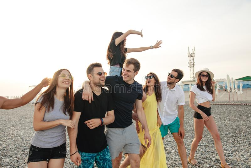 Il gruppo di amici che camminano alla spiaggia, divertendosi, il a due vie della donna sopra equipaggia, vacanza divertente fotografie stock libere da diritti