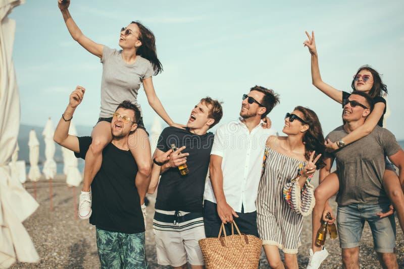 Il gruppo di amici che camminano alla spiaggia, divertendosi, il a due vie della donna sopra equipaggia, vacanza divertente immagini stock libere da diritti