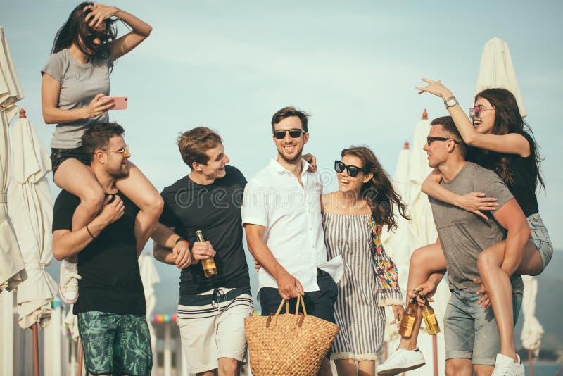 Il gruppo di amici che camminano alla spiaggia, divertendosi, il a due vie della donna sopra equipaggia, vacanza divertente immagini stock