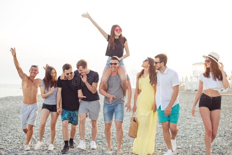 Il gruppo di amici che camminano alla spiaggia, divertendosi, il a due vie della donna sopra equipaggia, vacanza divertente immagine stock libera da diritti