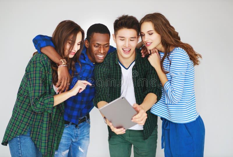 Il gruppo di amici felici della gente degli studenti con gli aggeggi delle compresse dei telefoni ride immagini stock libere da diritti