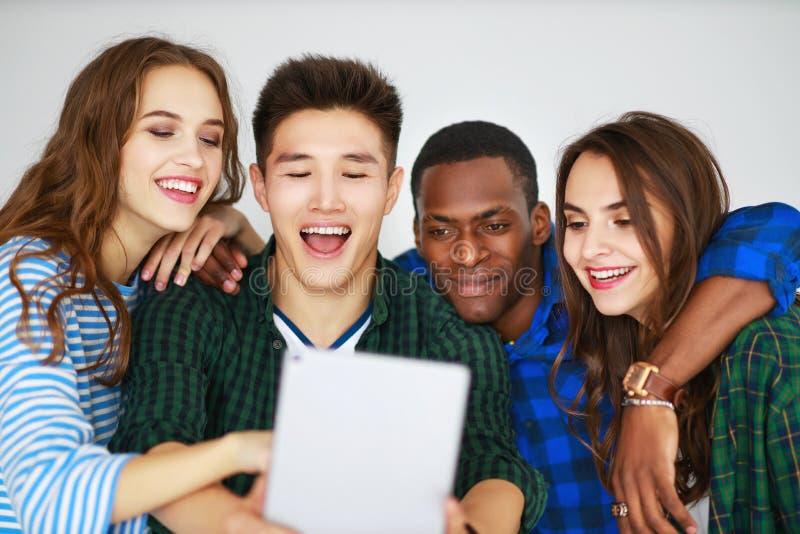 Il gruppo di amici felici della gente degli studenti con gli aggeggi delle compresse dei telefoni ride immagine stock