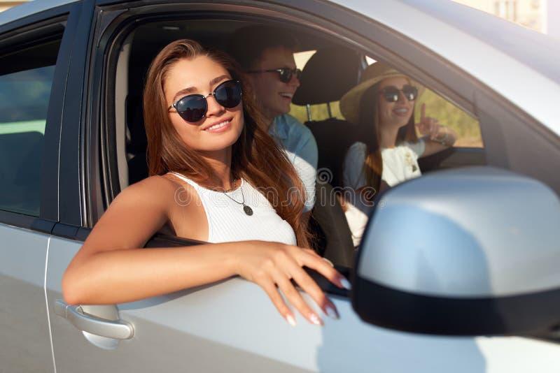 Il gruppo di amici ha affittato un'automobile sul viaggio stradale dell'estate ed è arrivato alla spiaggia del mare La donna in v immagini stock