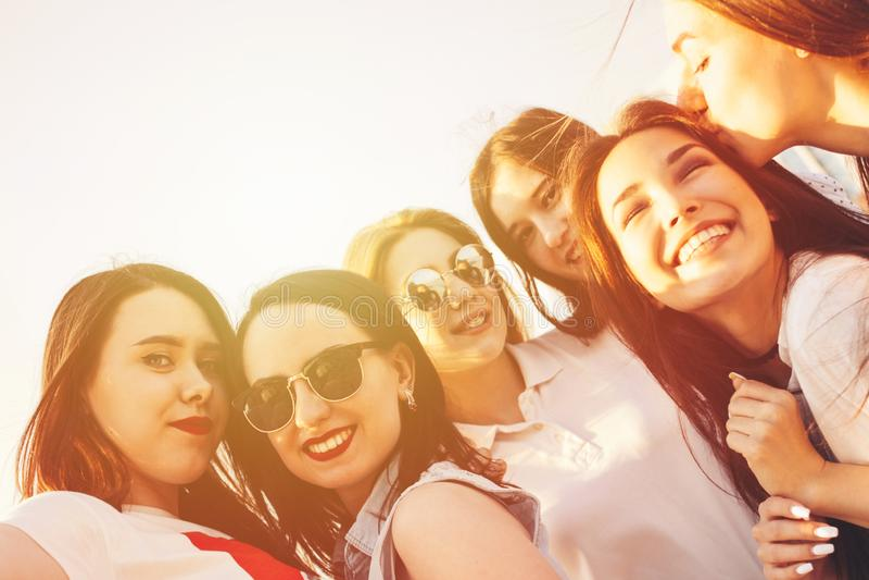Il gruppo di amici di ragazze felici spensierati gode della vita sulla via della città dell'estate, fondo tonificato luce solare  immagine stock libera da diritti