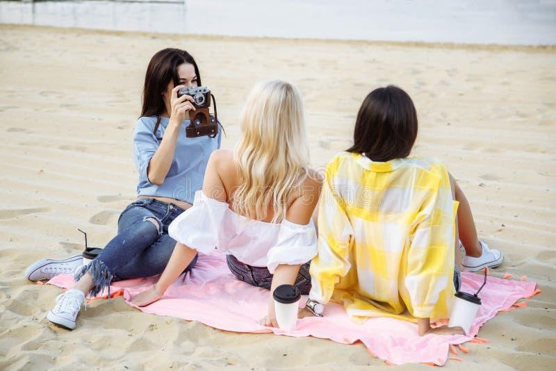 Il gruppo di amici di ragazze prende le foto sulla spiaggia immagini stock