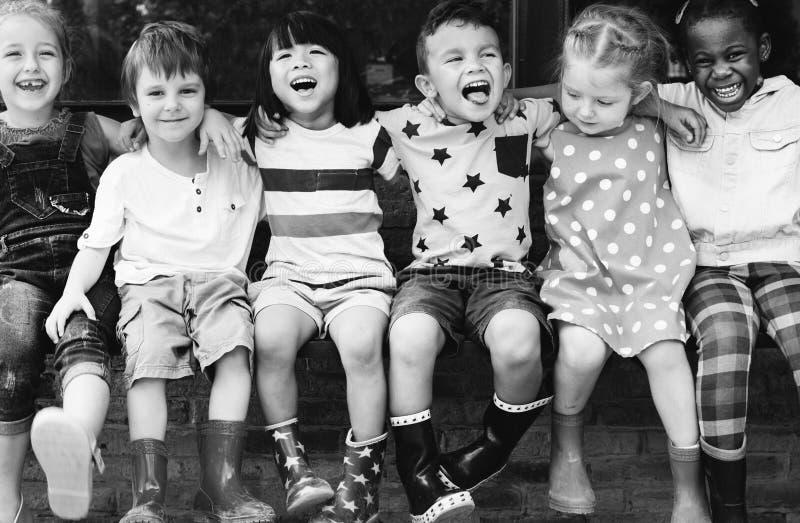Il gruppo di asilo scherza il braccio degli amici intorno alla seduta e allo smilin immagini stock