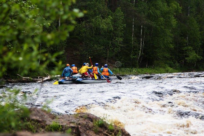 Il gruppo di atleti galleggia su un catamarano gonfiabile immagine stock