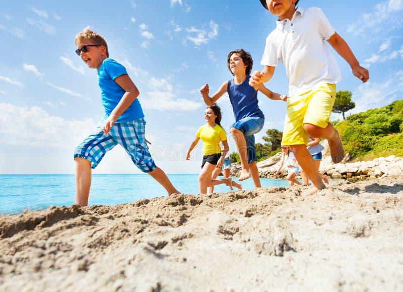 Il gruppo di bambini funziona insieme velocemente sulla spiaggia del mare immagini stock libere da diritti
