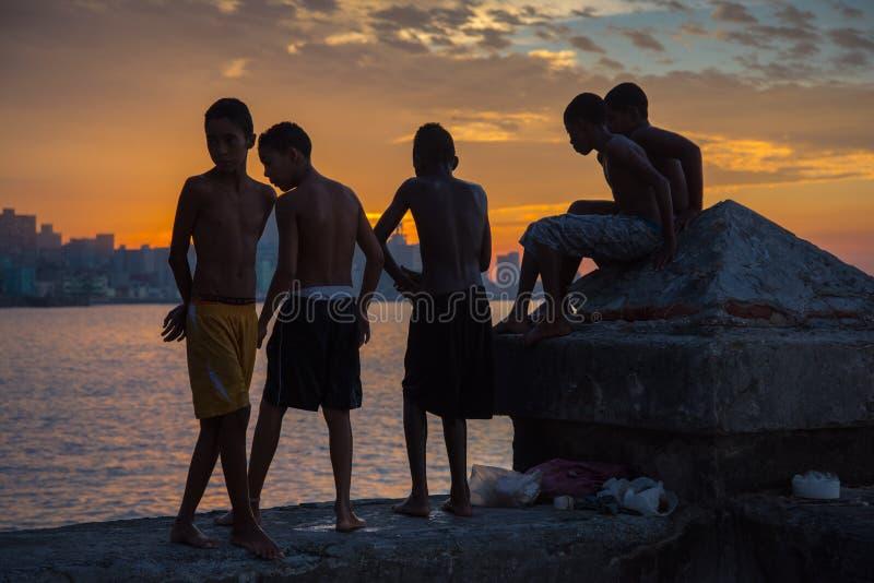 Il gruppo di bambini gioca e salta dalla parete di Malecon nell'Atlantico nella H fotografia stock libera da diritti