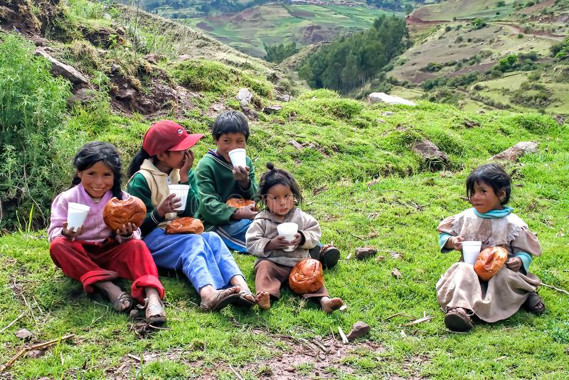 Il gruppo di bambini peruviani che dividono il Natale fa colazione sedendosi nell'erba che mangia il pane fotografia stock libera da diritti