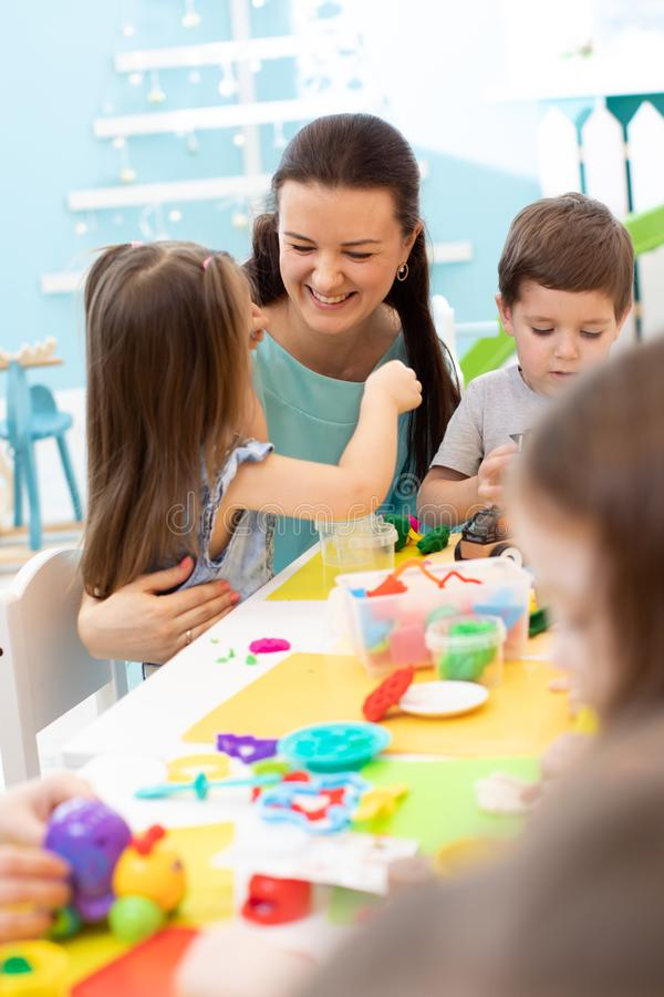 Il gruppo di bambini prescolari impegnati dentro handcrafts immagine stock