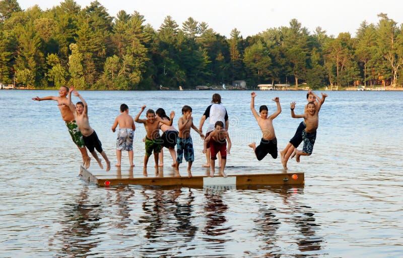 Il gruppo di bambini salta nel lago immagini stock libere da diritti