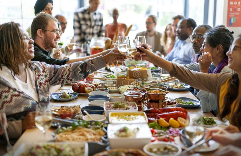 Il gruppo di diversa gente sta pranzando insieme fotografia stock libera da diritti
