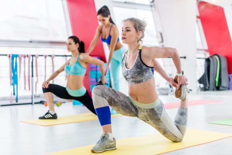 Il gruppo di donne che fanno i quadrati di inginocchiamento allunga l'esercizio mentre istruttore di forma fisica che aiuta nei p fotografie stock libere da diritti