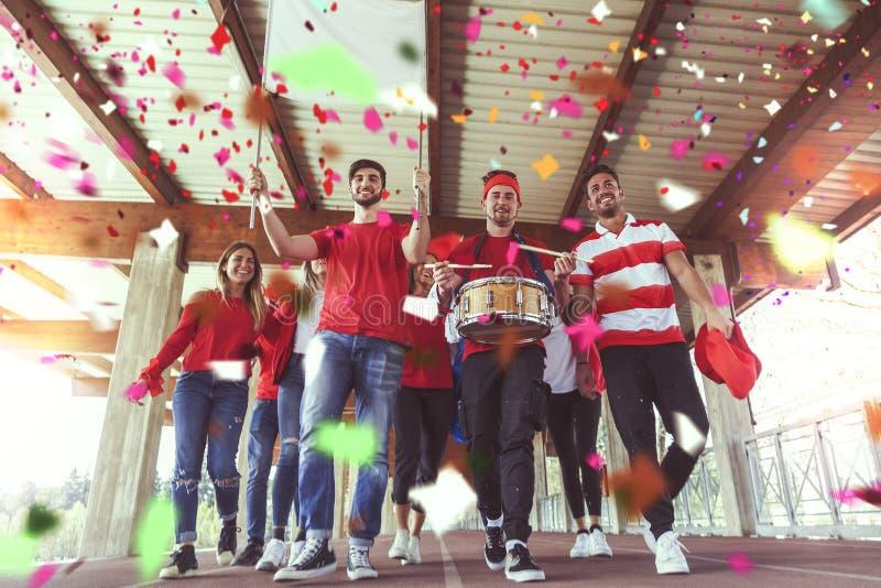 Il gruppo di fan si è vestito nel colore rosso che cammina sotto il tetto fotografia stock libera da diritti