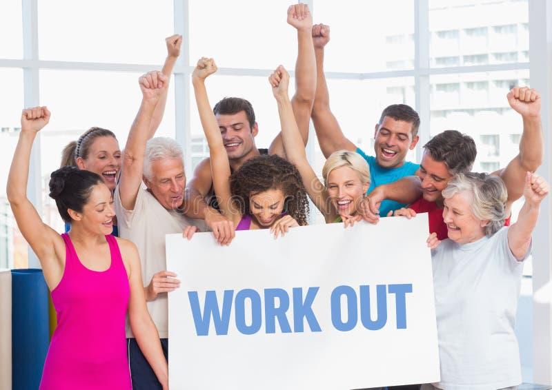 Il gruppo di forma fisica che sta con il cartello con risolve il testo in palestra immagini stock libere da diritti