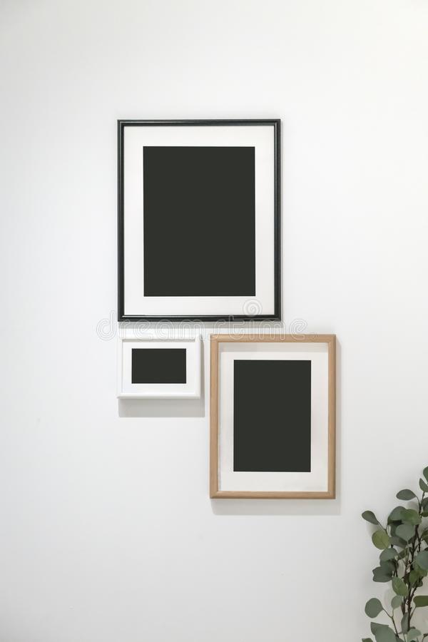 Il gruppo di foto incornicia l'attaccatura contro la parete bianca fotografia stock