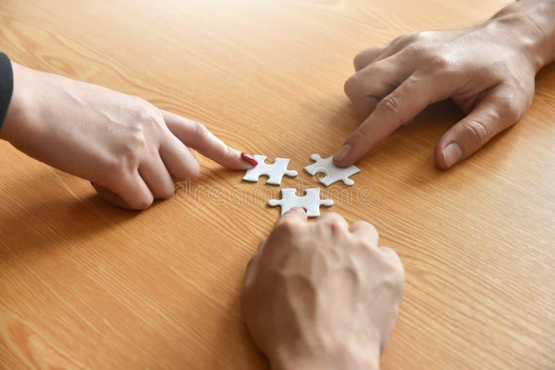 Il gruppo di gente di affari delle mani sta tenendo il puzzle immagine stock