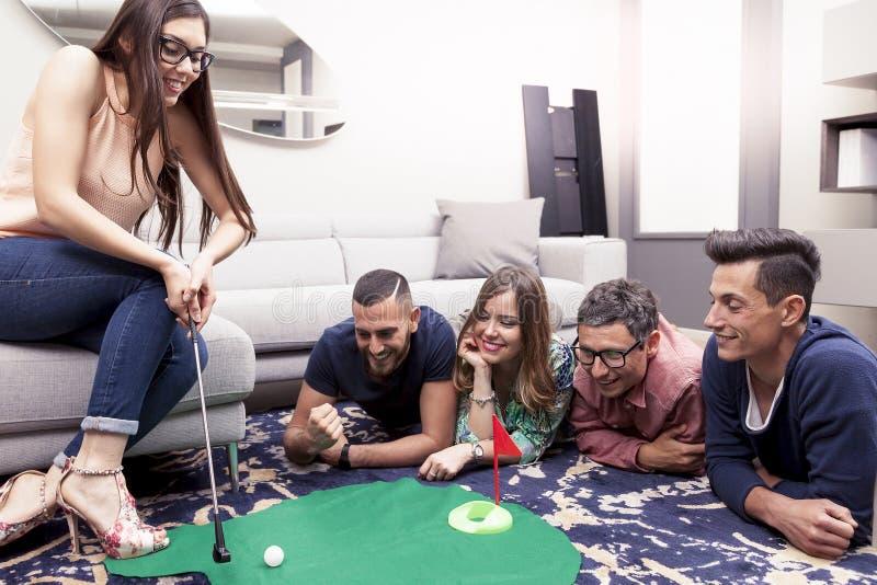 Il gruppo di giovani adulti si diverte giocando il golf nel salone immagine stock libera da diritti